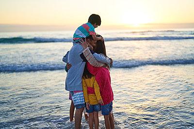 Happy affectionate family hugging in ocean surf at sunset - p1023m2200841 by Trevor Adeline