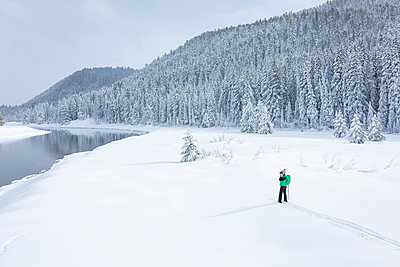 High angle view of female hiker photographing while standing on snow covered field - p1166m1406826 by Cavan Images