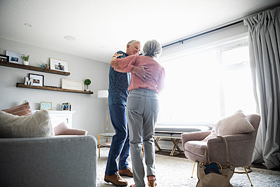Happy senior couple dancing in living room - p1192m2109896 by Hero Images