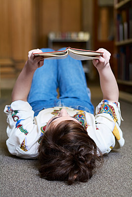 Female student reading book in a public library - p300m2103585 by Ivan Gener