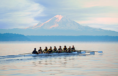 Team rowing boat in bay - p555m1478284 by Pete Saloutos