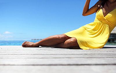 Woman in a yellow dress lying on a boardwalk - p045m669017 by Jasmin Sander