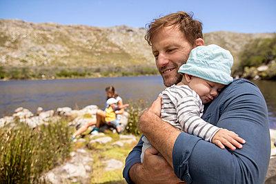 Familie mit Baby am Seeufer - p1355m1574018 von Tomasrodriguez