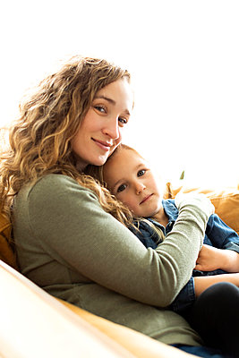 Mother and daughter sitting on sofa - p1427m2169168 by Jessica Peterson