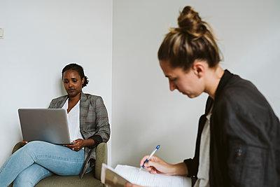 Women sitting and looking away - p312m2146291 by Stina Gränfors