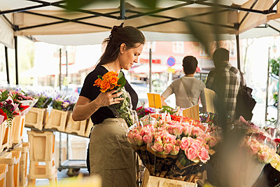 Side view of female owner working at flower shop - p426m1193091 by Maskot
