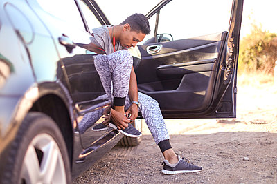 Young male runner putting tying trainer laces while sitting in car - p429m2075339 by Bean Creative