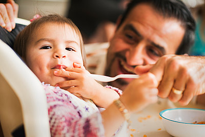 Hispanic father feeding daughter in high chair - p555m1464217 by Sollina Images