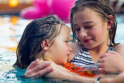 Caucasian girl holding brother in swimming pool - p555m1522928 by Marc Romanelli