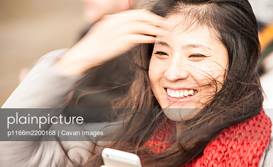 beautiful woman looking at her cellphone in windy weather - p1166m2200168 by Cavan Images
