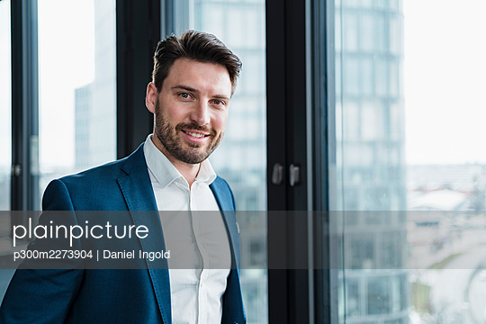Smiling male entrepreneur in blazer at work place - p300m2273904 by Daniel Ingold
