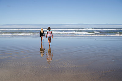 Rear view of girls walking on shore at beach against sky - p1166m1524561 by Cavan Images
