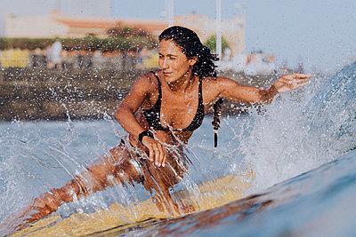Full length action of female surfer in bikini - p1166m2130036 by Cavan Images
