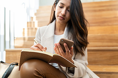 Young woman sitting on stairs using smartphone and taking notes - p300m2166194 by VITTA GALLERY