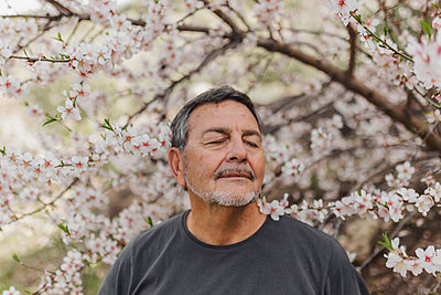 Man with eye closed in front of flower tree - p300m2281477 by PICUA ESTUDIO