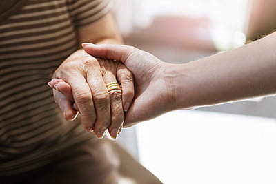 Cropped image of home caregiver holding hand of senior woman - p426m2072548 by Kentaroo Tryman