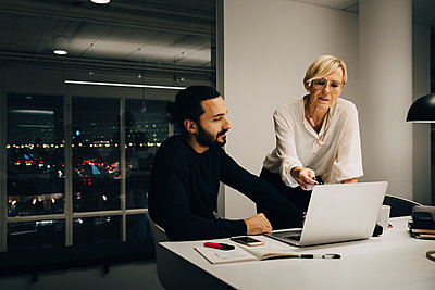 Male and female professionals planning strategy while discussing over laptop in illuminated office - p426m2194875 by Maskot
