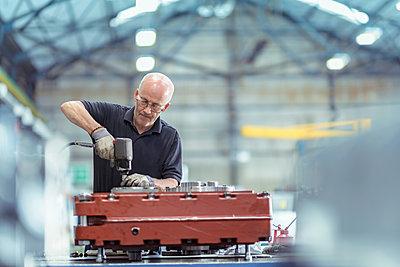 Engineer assembling gearbox in gearbox factory - p429m2019143 by Monty Rakusen