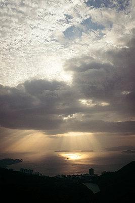 Sunbeams breaking through clouds over ocean - p795m2229305 by JanJasperKlein
