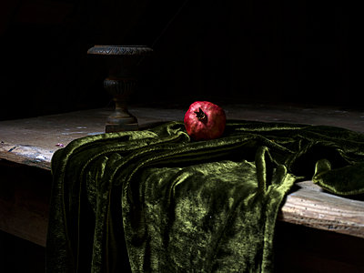 Pomegranate placed on green fabric - p945m1477166 by aurelia frey