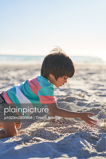 Boy playing in sand on sunny summer beach - p1023m2200868 by Trevor Adeline