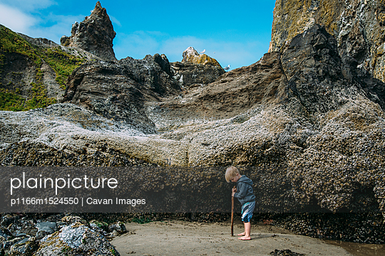 Side view of boy standing on sand by hill at beach - p1166m1524550 by Cavan Images