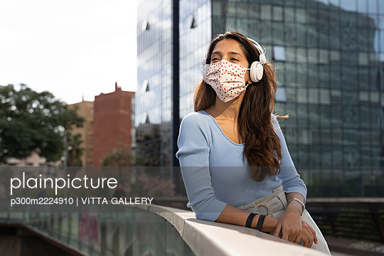 Businesswoman in protective face mask listening music on headphones while leaning on railing - p300m2224910 by VITTA GALLERY