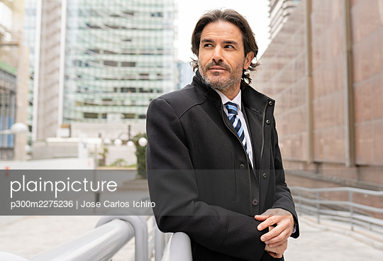 Contemplating male business professional looking away while leaning on railing in office park - p300m2275236 by Jose Carlos Ichiro