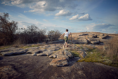 Rear view of boy holding stick while running on Arabia Mountain against sky - p1166m1560892 by Cavan Images