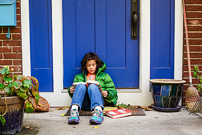 a young boy sits on his front stoop in autumn reading  a pile of books - p1166m2073806 by Cavan Images