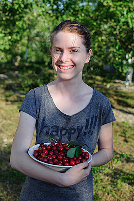 Teenager holding a plate with sweet cherries - p1412m1584259 by Svetlana Shemeleva