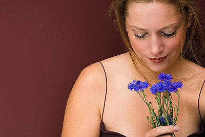 Young woman holding cornflowers - p3007580f by Patrick Jelen