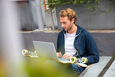 Young man sitting on steps, using laptop on longboard - p300m2156541 by Robijn Page