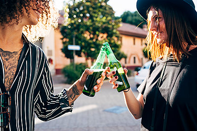 Happy couple toasting beer bottles while standing in city - p300m2206875 by Eugenio Marongiu