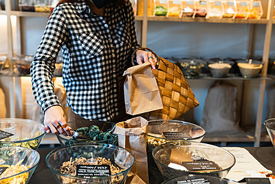 Woman putting spice in paper bag at store - p300m2286893 by NOVELLIMAGE