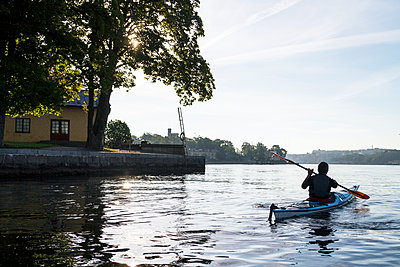 Man kayaking on sea - p312m1103790f by Henrik Trygg