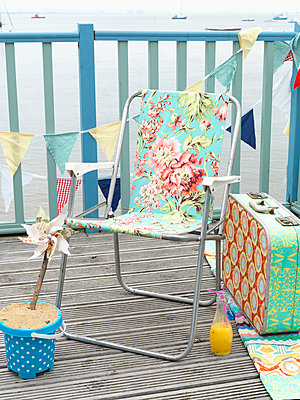 Floral patterned folding chair with vintage suitcase on coastal decking with bunting - p349m919995 by Fiona Kennedy