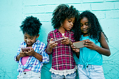 Girls leaning on wall texting on cell phones - p555m1472922 by Peathegee Inc