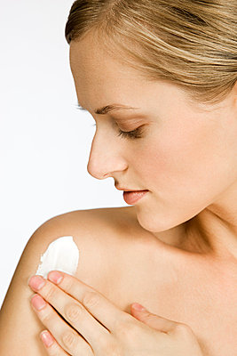 Woman applying body lotion - p9245838f by Image Source