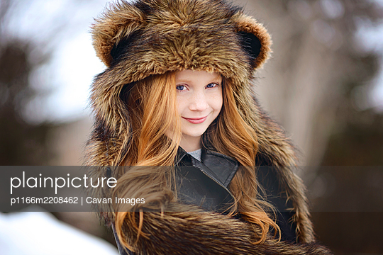 Young Girl Long Red Hair Wearing Bear Spirit Hood - p1166m2208462 by Cavan Images