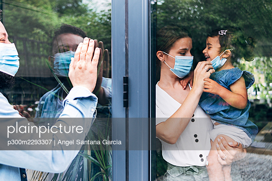Father greeting family through glass door during COVID-19 - p300m2293307 by Angel Santana Garcia