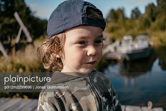 Smiling boy looking away - p312m2299696 by Jonas Gunnarsson