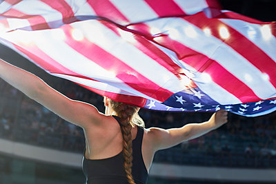 Female athlete running victory lap with American flag - p1023m1217714 by Chris Ryan
