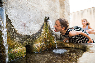 Girl drinking water from fountain while standing by sister outdoors - p1166m1555019 by Cavan Images