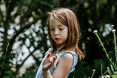 Young girl looking down at a small white flower in her hand - p1166m2207960 by Cavan Images