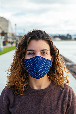 Young womman on the street wearing a face mask - p1166m2246858 by Cavan Images