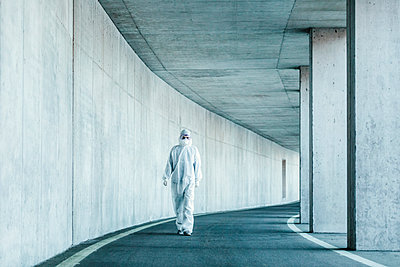 Man wearing protective clothing walking in a tunnel - p300m2170942 by Valentin Weinhäupl