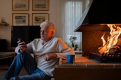 Senior man using mobile phone while sitting by fireplace at home - p300m2242190 by VITTA GALLERY