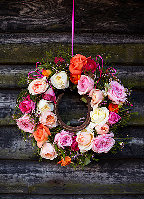 Wreath of cut roses with horse shoe hang on exterior of wood cabin in late summer. - p349m2167854 by Sussie Bell