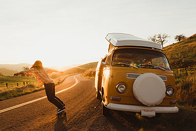 Young male skateboarder skateboarding on rural road at sunset, Exeter, California, USA - p924m1494861 by Peter Amend